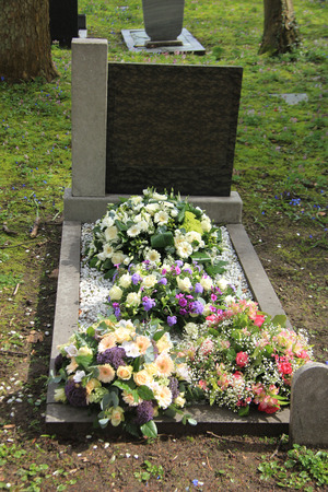 sympathy: Multicolored sympathy flowers on an old grave Stock Photo