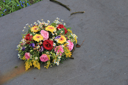 sympathy: Multicolored sympathy flowers on a grey tombstone Stock Photo