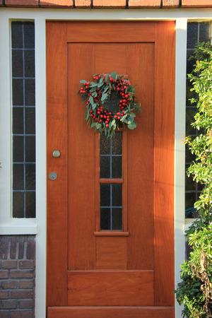 ドアの上の装飾とベリー クリスマスの花輪 写真素材