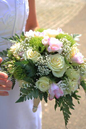 bruidsboeket: Bruid die haar bruidsboeket, ivoor rozen en roze fresia