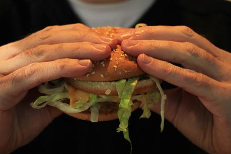 nutricion: Man holding his hamburger, close up of hamburger Stock Photo