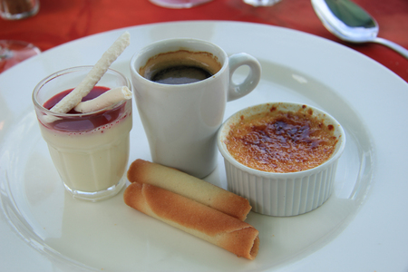 blancmange: French dessert: Creme brûlée, blancmange with berry sauce and meringue and an espresso