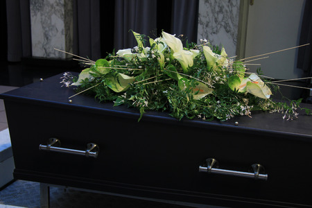cremation: Funeral flowers on a casket, funeral service