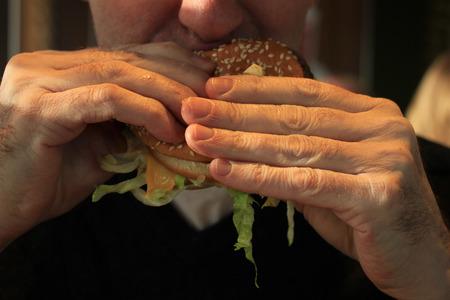 Man holding his hamburger, close up of hamburger photo