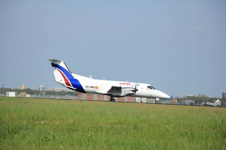 scheduled: May,11th 2015,  Schiphol Airport the Netherlands:EC-IMX Swiftair Embraer EMB-120FC Brasilia on the Polderbaan runway of Amsterdam Schiphol Airport.  Swiftair, founded in 1986, headquartered in Madrid, Spain. It operates scheduled and charter, passenger an