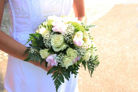 bridal bouquet: Bride holding her bridal bouquet, ivory roses and pink fresia Stock Photo