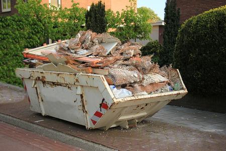 Geladen Müllcontainer in der Nähe einer Baustelle, Renovierungs Lizenzfreie Bilder