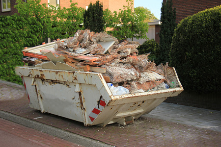 Loaded dumpster near a construction site, home renovation photo