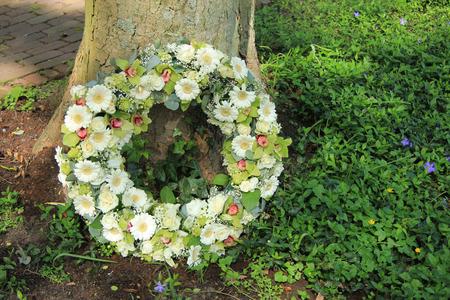 sympathy: Sympathy wreath near a tree, various sorts of white flowers Stock Photo