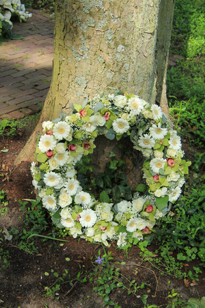 sympathy flowers: Sympathy wreath near a tree, various sorts of white flowers Stock Photo