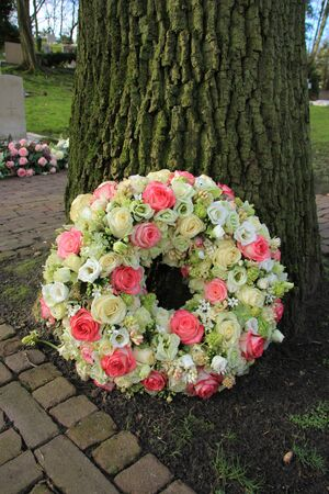 sympathy: Sympathy wreath near a tree, pink and white roses