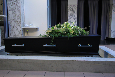 cremation: Wooden casket with funeral flowers, cremation ceremony