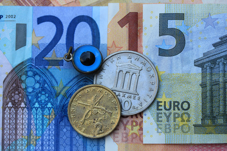 evil eye: Greek Euro crisis 2015: vintage Greek Drachma coins on Euro notes and the Greek evil eye