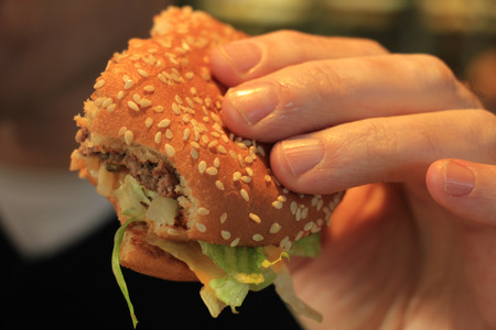 sesame seed: Man holding his hamburger, close up of hamburger Stock Photo