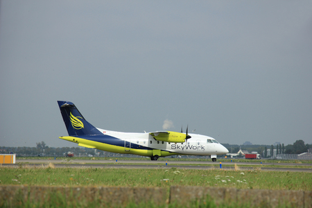 polderbaan: Amsterdam, The Netherlands - August 10 2015: HB-AEO SkyWork Airlines Dornier Do-328  taxing on the Polderbaan runway to the main terminal of Amsterdam Schiphol Airport