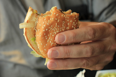 sesame seed: Man holding a fresh made hamburger Stock Photo