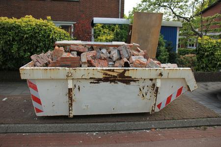 dumpster: Loaded dumpster near a construction site, home renovation