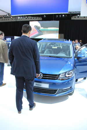 autos: Amsterdam, The Netherlands - April 23, 2015: Volkswagen Sharan admired by potential buyer at the 2015 Amsterdam AutoRAI motorshow. The 2015 Amsterdam motorshow was running from April 17 until April 26, in the RAI event center in Amsterdam, The Netherlands Editorial