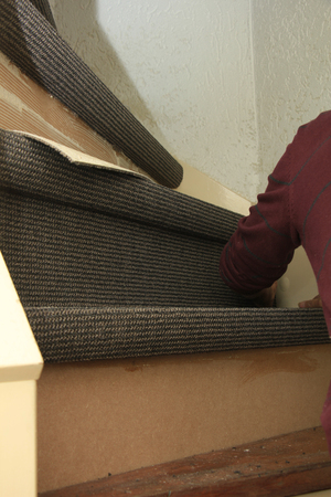 carpeting: Craftsman carpeting a staircase with vintage tools
