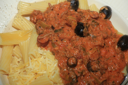 porting: Pasta on a plate: Penne with ragu, cheese and black olives