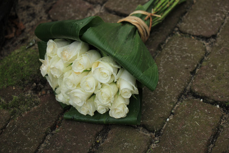 sympathy: White sympathy roses in a small bouquet on the pavement
