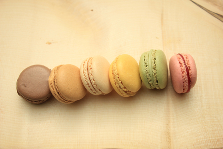 flavors: Macarons in different colors and flavors on a wooden cutboard