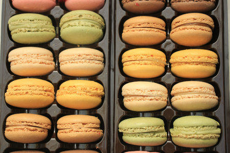 flavors: Macarons in different colors and flavors in a plastic tray