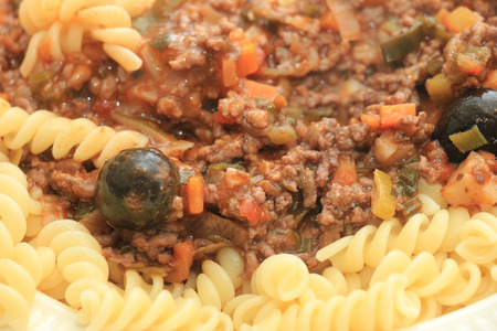 porting: Pasta on a plate: Fusilli with ragu, cheese and black olives