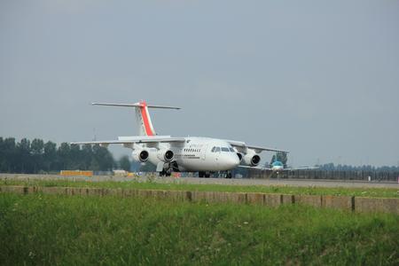 polderbaan: Amsterdam, The Netherlands - August 10 2015: EI-RJU Cityjet British Aerospace Avro RJ85 taxing on the Polderbaan runway to the main terminal of Amsterdam Schiphol Airport