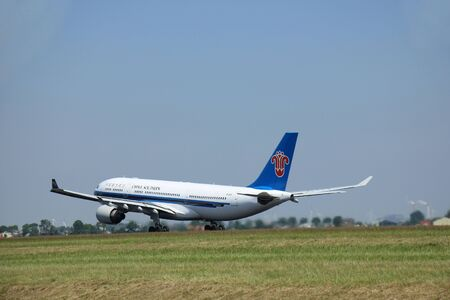 polderbaan: Amsterdam, The Netherlands - June 12 2015: B-6515 China Southern Airlines Airbus A330-200  takes of from Amsterdam Airport Polderbaan runway. Editorial