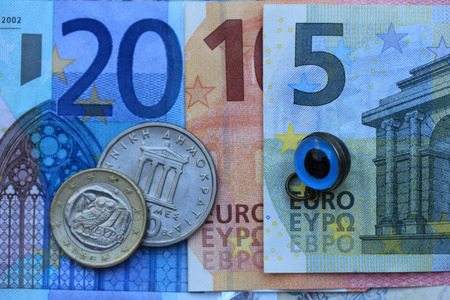 greek coins: Greek Euro crisis 2015: vintage Greek Drachma coins on Euro notes and the Greek evil eye