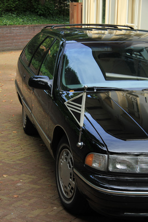 mortician: Black hearse, parked outside a funeral home
