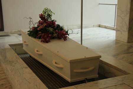 crematorium: White coffin with funeral flowers in a crematorium