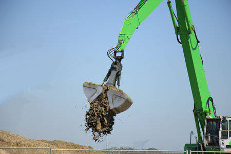scooping: Green excavator scooping sand, putting it on a pile