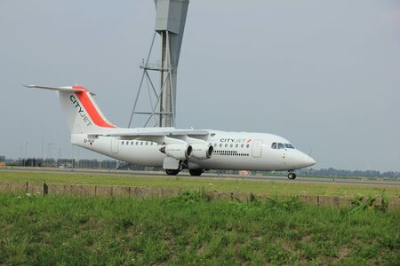 aerospace: Amsterdam, The Netherlands - August 10 2015: EI-RJU Cityjet British Aerospace Avro RJ85 taxing on the Polderbaan runway to the main terminal of Amsterdam Schiphol Airport