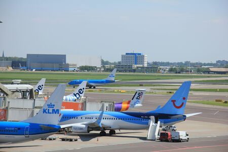 may fly: Amsterdam The Netherlands -  May 13th 2016: planes from Fly Be, TUI and KLM parked at gate at Schiphol International Airport Editorial