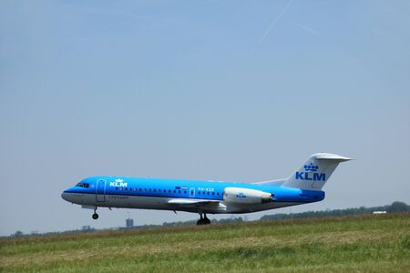 polderbaan: Amsterdam, The Netherlands - June 12 2015: PH-KZK KLM Cityhopper Fokker F70  takes of from Amsterdam Airport Polderbaan runway.