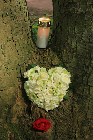 sympathy: Heartshaped sympathy flowers and candle Stock Photo