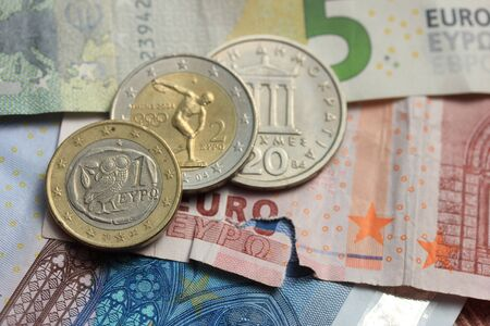 greek currency: Old Greek and modern greek euro coins on Euro bank notes