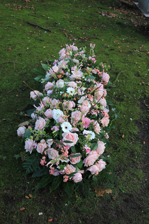sympathy: Sympathy flowers in pink and white on a grave