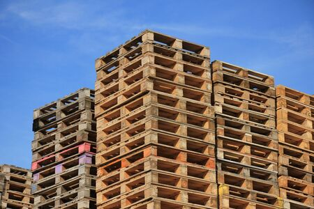 stackable: Stacked wooden pallets at a storage Stock Photo