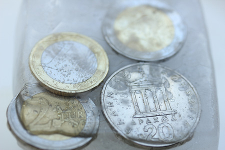 greek coins: Frozen Assets: Greek euro and Drachme coins in ice