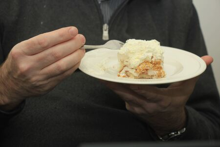 small plate: Man eating a piece of cake from a small plate Stock Photo