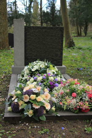 sympathy flowers: Multicolored sympathy flowers on an old grave Stock Photo