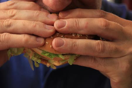 nutricion: Man eating a fresh made hamburger