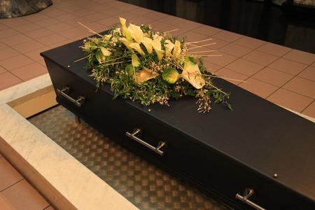 crematorium: Wooden casket with funeral flowers in a crematorium hall Stock Photo