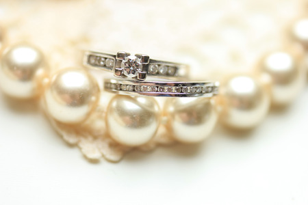 wedding band: Engagement ring and wedding band with diamonds on a pearl necklace Stock Photo