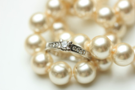 carat: Diamond engagement ring in a channel setting and a pearl necklace