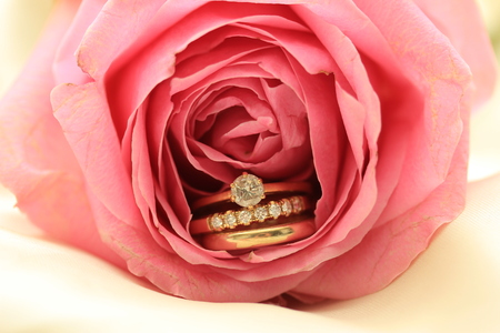 diamond rings: Diamond wedding rings and plain band in pink rose Stock Photo