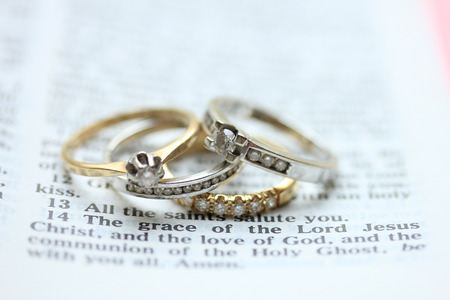 verse: Two wedding sets, one in yellow gold, one in white gold for a double bride wedding on a bible verse Stock Photo